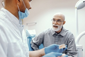 An older man speaking with a dentist.