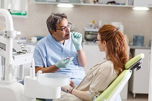 Dentist talking to female patient in dental exam room
