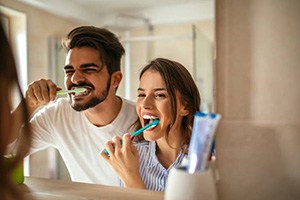 Young man and woman brushing teeth together