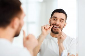 Bearded man with white shirt flossing in the mirror